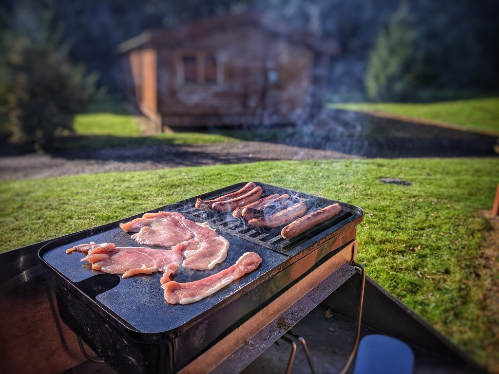 Sausage and Bacon cooking on the Plancha